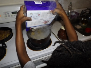 Young boy cooking pasta