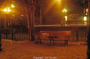 Pioneer Square at night with downtown city lights with a homeless man sleeping on a park bench Seattle Washington State USA